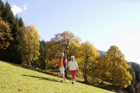 active adult community: Senior couple Nordic walking outdoors