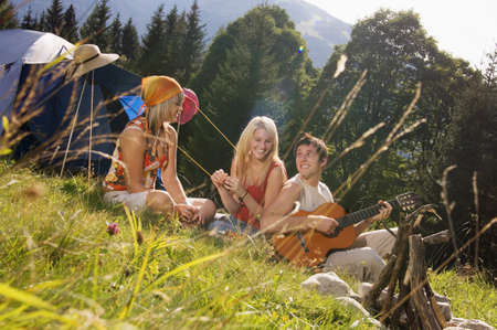 easygoing: Young people in meadow, man playing guitar, tilt view LANG_EVOIMAGES