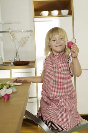 4 of a kind: Girl (2-4) in kitchen,holding radish,close-up