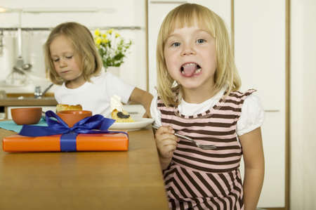 pert: Two little girls eating cake in kitchen LANG_EVOIMAGES
