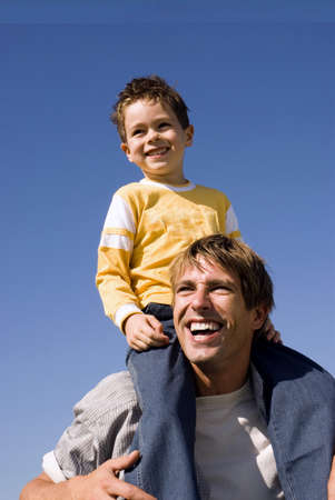 kind hearted: Boy (4-7) sitting on fathers shoulders, smiling, close-up