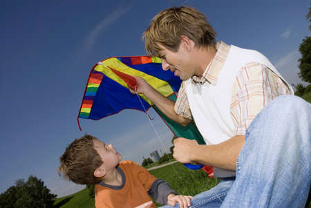 confiding: Father and son (4-7) with kite, close-up