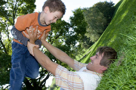 confiding: Father lying on grass and holding up son (4-7), smiling