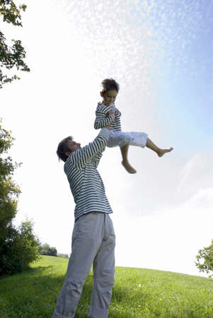 easygoing: Father lifting son (4-7) in park, side view