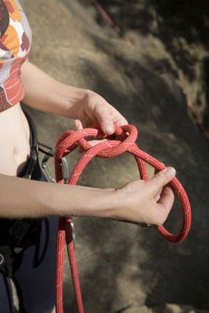 unrecognisable person: Woman knotting climbing rope,mid section LANG_EVOIMAGES