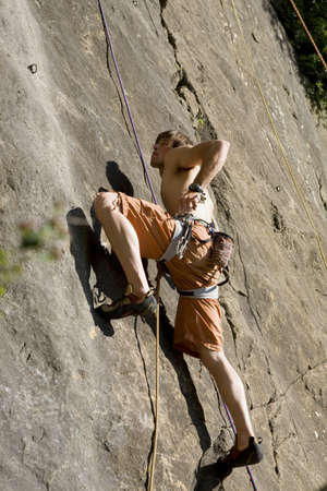non moving activity: Young man rock climbing,low angle view LANG_EVOIMAGES