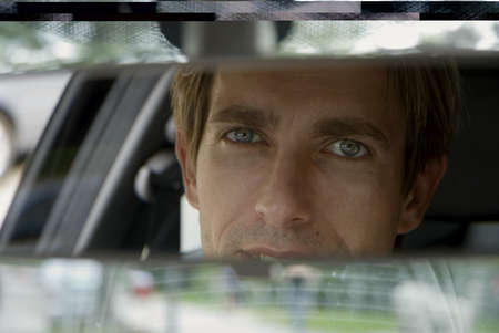 frontal views: Businessman looking into rear view mirror, close-up