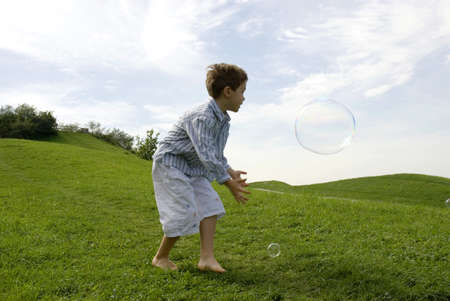 kind hearted: Boy (4-7) playing with soap bubble, side view