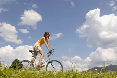 smile please: Young woman riding bicycle in meadow, side view