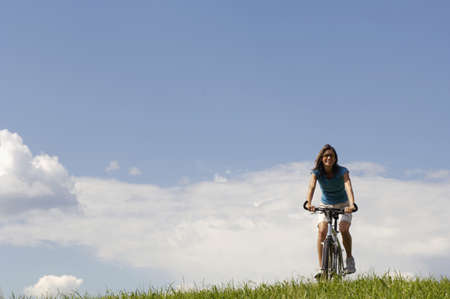 non moving activity: Young woman riding bicycle in meadow LANG_EVOIMAGES