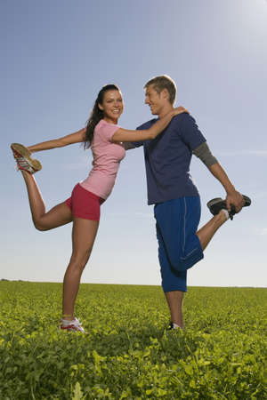 exerting: Young couple exerting gymnastic on meadow, side view LANG_EVOIMAGES