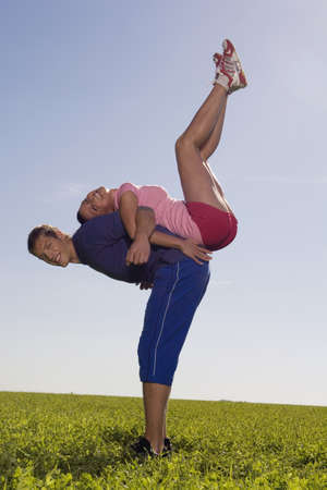 mirthful: Young couple exercing gymnastic on meadow, side view