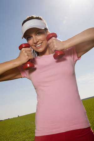 exert: Young woman exercising with dumbbells, smiling, tilt view