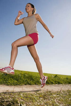 non moving activity: Young woman jogging, low angle view LANG_EVOIMAGES