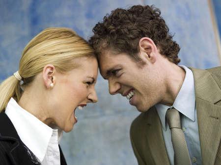 dissension: Businessman and businesswoman quarrelling, side view, close up LANG_EVOIMAGES