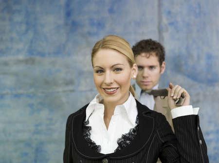 Businesswoman pulling businessman's tie, smiling Stock Photo - 23853126