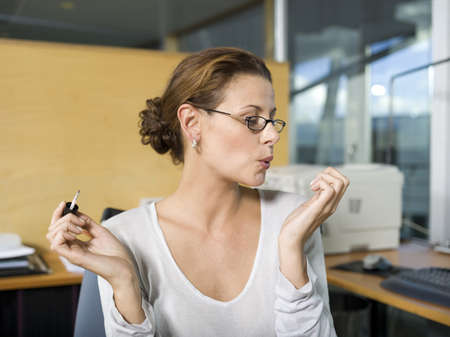 in low spirits: Woman in office, applying nail polish, blowing, close-up