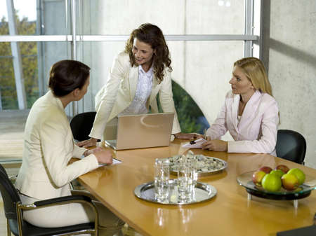 Businesswomen sitting at desk with laptop Stock Photo - 23853140