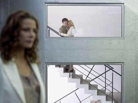grudging: Couple embracing on staircase, (focus on background) LANG_EVOIMAGES