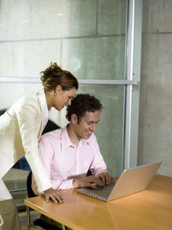 Man and woman in office, using laptop, smiling Stock Photo - 23853159