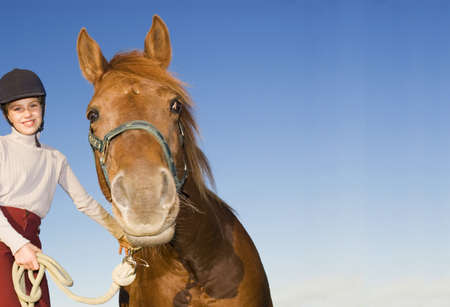 mirthful: Girl (10-12) with pony, portrait, low angle view