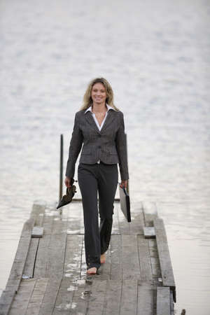 pantsuit: Businesswoman walking on jetty, holding shoes in hand LANG_EVOIMAGES