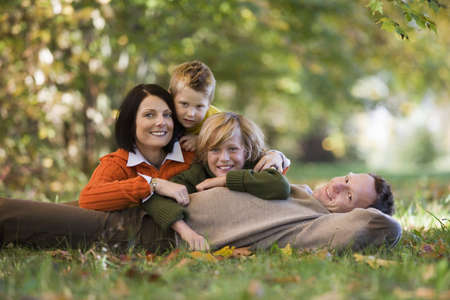 4 of a kind: Parents with two sons lying in meadow