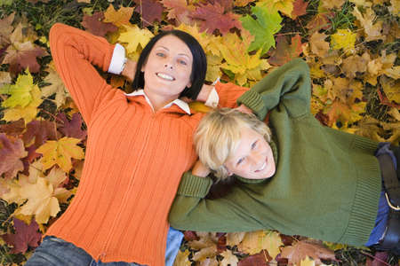 confiding: Mother and son (8-11) lying on autumn leaves, elevated view, portrait