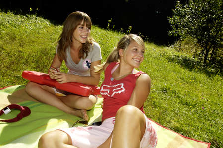 18 19 years: Teenage girls (16-17) sitting in meadow, looking away, smiling