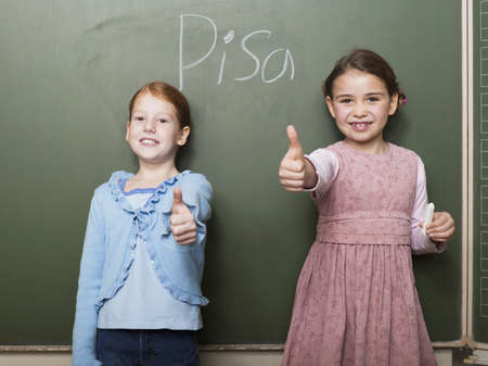 high school series: Girls (4-7) standing by blackboard, showing thumbs up sign