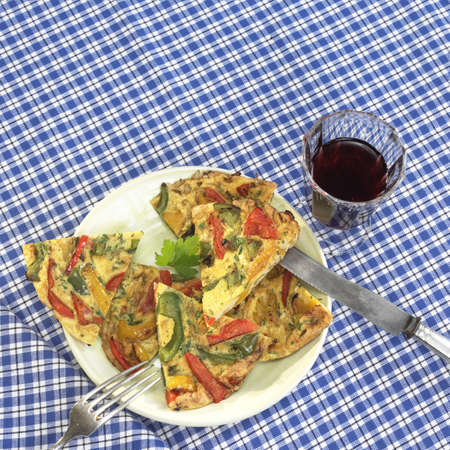 red cross red bird: Spanish tortilla on plate with glass of wine