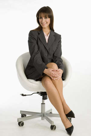 legs crossed at knee: Businesswoman sitting on chair, smiling, portrait