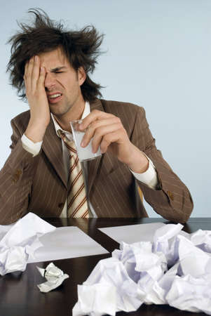 raged: Businessman sitting on desk with head in hands, papers around