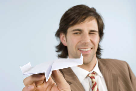 employe: Businessman holding paper plane, winking, smiling, close-up