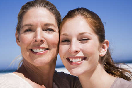 confiding: Mother and daughter on beach, smiling, close-up, portrait LANG_EVOIMAGES