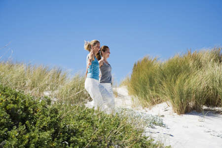 kind hearted: Mother and daughter running on beach, hand in hand LANG_EVOIMAGES