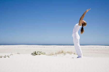 age 40 45 years: Woman exercising yoga on beach