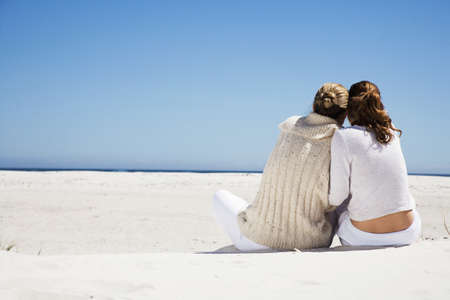 confiding: Mother and daughter sitting on beach, rear view