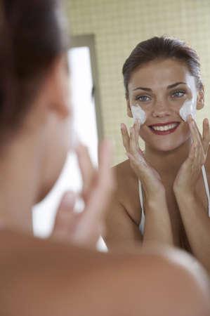 cremas faciales: Mujer joven que aplica la crema de cara LANG_EVOIMAGES