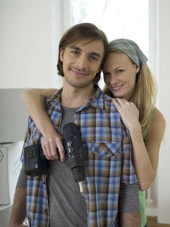 accrued: Woman embracing man, holding drill
