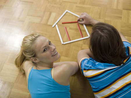 accrued: Couple lying on floor, building house with pens