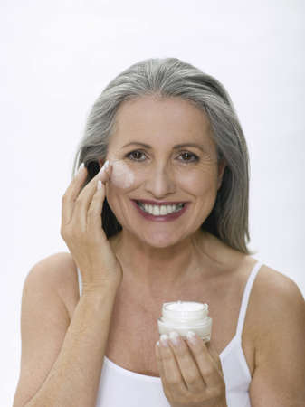 aging woman: Senior woman applying face cream, portrait