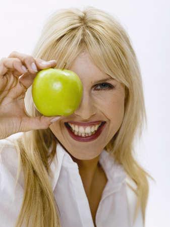 accrued: Woman holding green apple, portrait LANG_EVOIMAGES