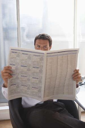 interiour shots: Business man reading newspaper LANG_EVOIMAGES