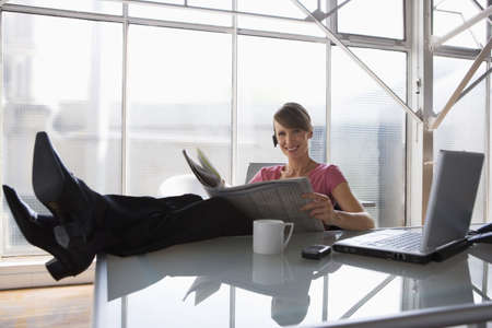 30 35 years women: Business woman relaxing at her desk feet on table top