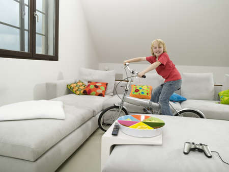 Boy cycling in living room Stock Photo - 23853299