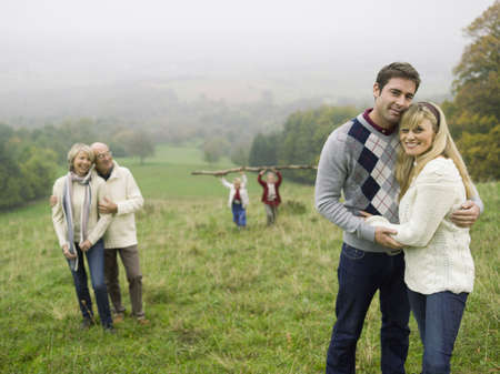Germany, Baden-Württemberg, Swabian mountains, Two couples embracing, children in background LANG_EVOIMAGES