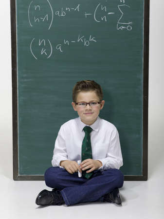 Boy (10-11) sitting in front of blackboard, portrait Stock Photo - 23853324