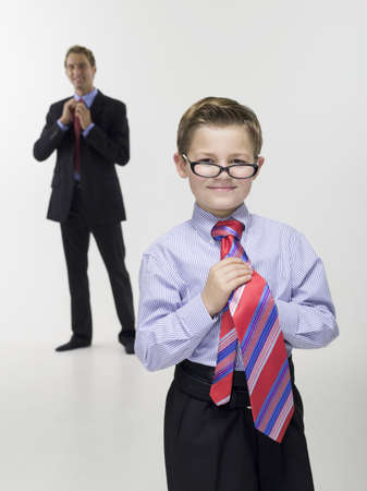 two generations: Father and son (8-9) in business clothing, portrait