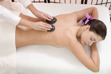 hot stone massage: Young woman receiving hot stone massage, elevated view